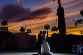 Embracing couple at wedding in Southern Arizona with colorful sunset sky.