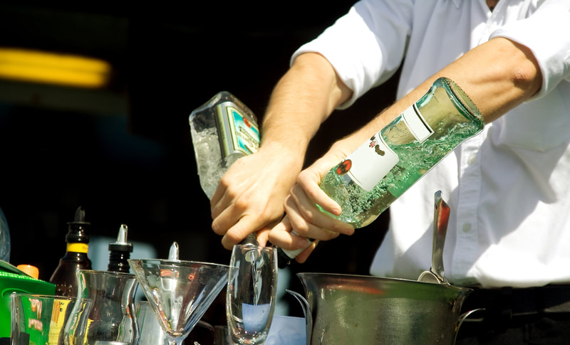Bartending staff pouring liquor for a cocktail