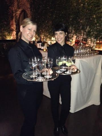 Catering servers passing beverages at formal event.